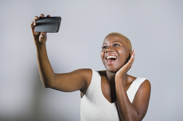 young beautiful and happy black afro American woman smiling excited taking selfie picture portrait with mobile phone or recording self portrait video