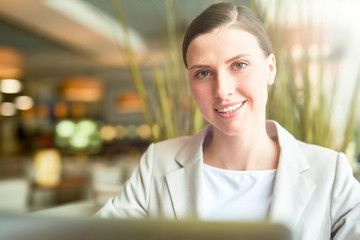 Portrait of young attractive Caucasian woman in elegant formal wear smiling at camera happily on blurred restaurant background