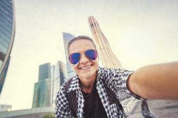 Beautiful young woman girl doing selfie on a smartphone on the background of the business center of Moscow City, traveling to Russia