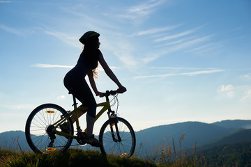 Silhouette of strong female biker cycling on mountain bike in the sunny morning, wearing helmet, against blue sky. Outdoor sport activity, lifestyle concept. Copy space