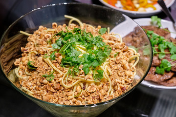 Dry spaghetti noodles with ground nuts and parsley in bowl