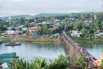 Tourists crowd travel on wooden mon bridge landmark in sangkhlaburi