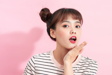 Beautiful teenage girl with buns on a pink background.