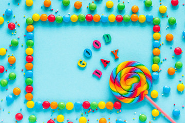Rainbow candy background, Text GOOD DAY, colored letters, greeting card, candy and lollipops, blue background, Top view, Flat Lay