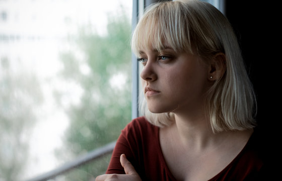 Close up of crying depressed young blond woman near window at home. Sadness, nostlagic, depression.