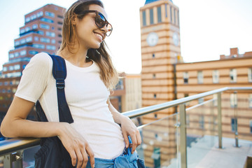 portrait of a young smiling attractive woman with sunglasses at sunny day . woman walking and poses in cityscape.