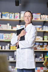 Beautiful pharmacist using notepad at the pharmacy