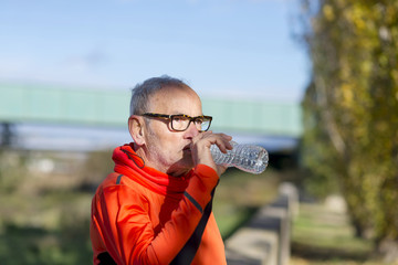 Handsome senior jogging man drinking fresh water from bottle after morning run