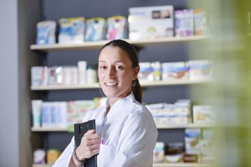 Beautiful pharmacist using notepad at the pharmacy