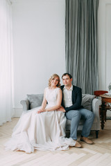 Beautiful couple in wedding photo shoot. Loft Studio in European style, bright and with large Windows. Loving people with happy faces. Bridal bouquet and stylish decorative.