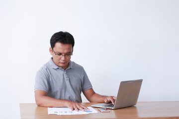 Handsome businessman is working with laptop in office Online