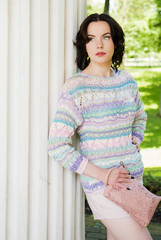 The woman in a fashionable, knitted pullover poses outdoors