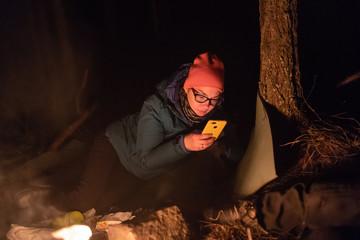 Traveler woman sitting near campfire