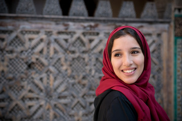 Portrait of muslim woman smiling in traditional clothing with red hijab