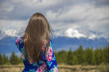 the girl stands and looks at the mountains
