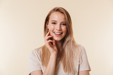 Portrait of gorgeous woman 20s with european appearance in basic t-shirt smiling at camera, isolated over beige background in studio