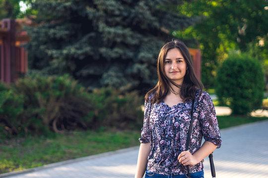 Girl walks in city with blue handbag