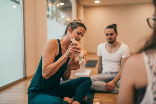 Yoga instructor showing anatomy of a knee joint