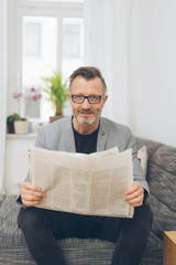 Mature metro man reading newspaper in lounge room