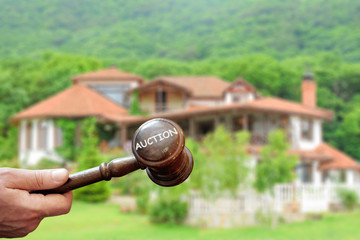 Concept real estate auction,blurred house background and wooden gavel in a hand