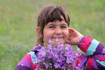 Kleines lächelndes Mädchen mit Wiesen-Glockenblumen  Campanula patula