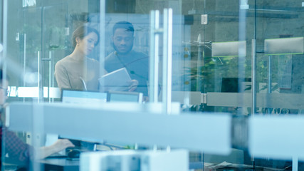 Busy International Office, Beautiful Caucasian Woman Shows Documents to a Black Colleague while Walking Through Glass Hallway. In the Background Diverse Group of Creative Colleagues Working.