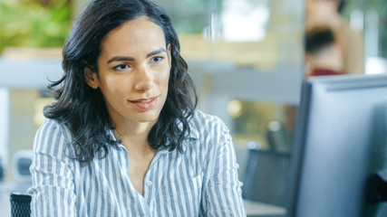Portrait Shot of a Beautiful Young Hispanic Woman sits at Her Desk and Works on a Personal Computer. In the Background Busy Office with Working Colleagues.