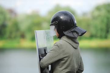 Security service specialist in uniform and helmet standing against lake