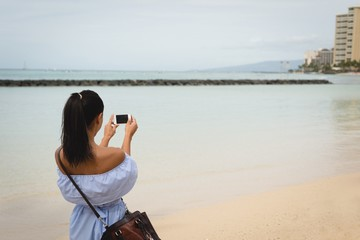 Woman clicking photo of sea with mobile phone