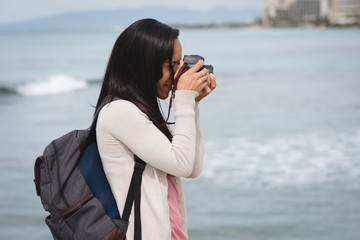 Woman photographing with digital camera at beach