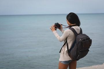 Woman clicking photo of sea with digital camera at beach