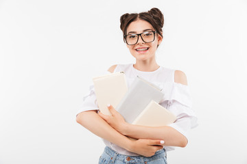 Photo of beautiful teenage girl 20s with double buns hairstyle and dental braces smiling and holding many studying books, isolated over white background