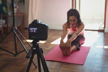 Female video blogger recording video vlog while exercising