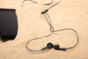 Mobile phone  with headphones on sand in a beach ..
