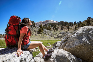 Summer hike in the mountains with a backpack and tent along the path to the top.