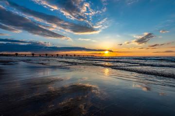odbicie chmur w mokrym piasku podczas zachodu słońca