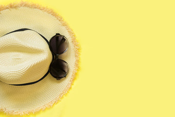 Straw beach female's hat and black sunglasses on yellow background. Top view. Flat lay.