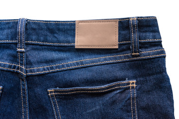 Back of blue jeans with leather jeans label sewed on blue jeans. Isolated on white background with clipping path.
