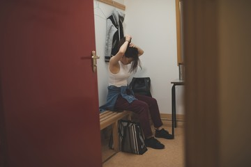 Female dancer tying her hairs in changing room
