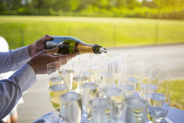 Waiter pouring champagne or sparkling wine to glasses at an event