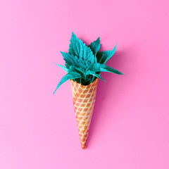 Ice cream cone with turquoise leaves on pink background. Minimal nature summer concept. Flat lay