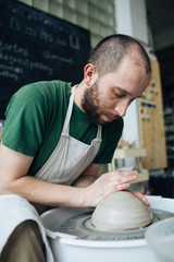 Handcrafted on a potter's wheel,Hands make clay from various items for home and sale in the store and at the exhibition, ceramic items are made in hand, stylish bearded young man makes products