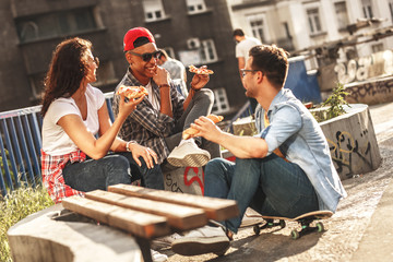 Group of friends hangout at the street.They  eating pizza.Fast food concept.