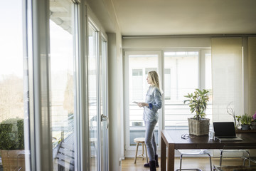Woman with tablet looking out of window