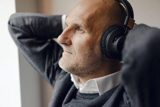 Senior man wearing headphones, listening music, portrait