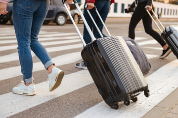 Cropped image of three women from back walking across pedestrian crossing, and carrying luggage to airport. Air travel or holiday concept
