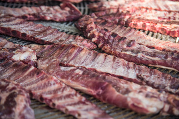 Fresh raw meat ribs with salt and pepper on big metal grill. Selective focus.4