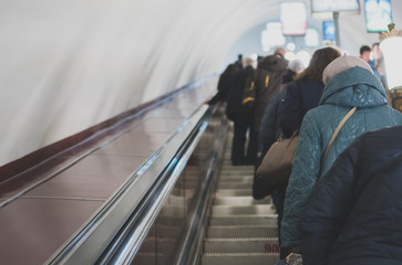 People riding the escalator in metro station.
