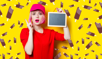 portrait of beautiful surprised young woman with little blackboard on the wonderful yellow studio background