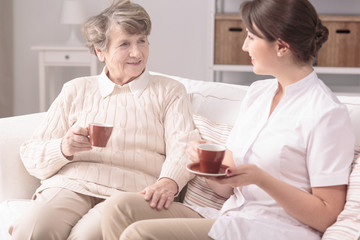 Elderly woman and her private carer sitting together on a sofa, drinking tea at home